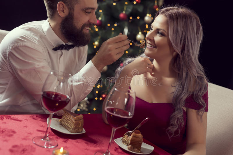 Romantic dinner. Beautiful young couple having a conversation on a romantic Christmas dinner, drinking wine and eating cake stock photography