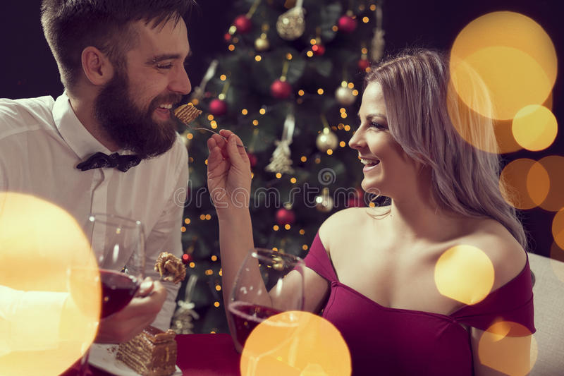 Romantic dinner. Beautiful young couple having a conversation on a romantic Christmas dinner, drinking wine and eating cake. Focus on the girl stock photos