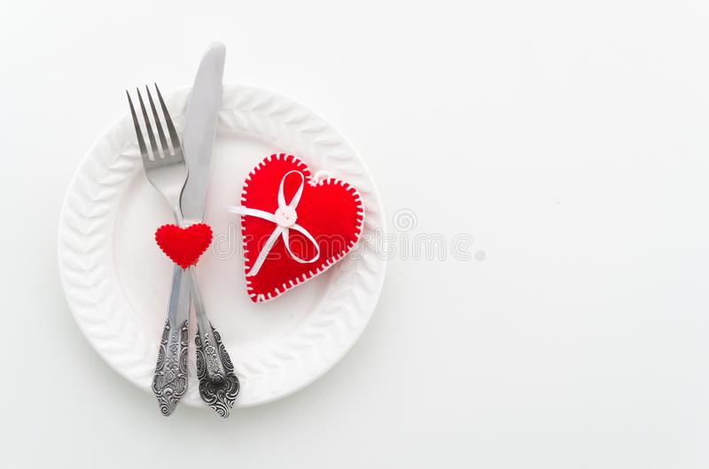 Romantic dinner concept. Ceramic plate with cutlery and felt hearts. Top view with copy space for banner design royalty free stock image