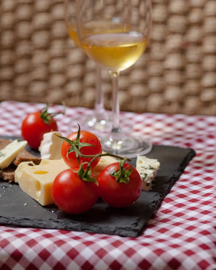 Romantic dinner for a couple on Saint Valentine`s day. Two glasses of cold white wine and gourmet french cheese plate with bread and fresh tomatoes. Nicely stock image