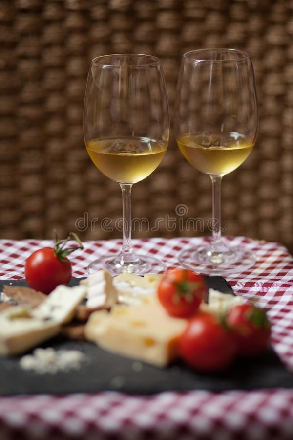 Romantic dinner for a couple on Saint Valentine`s day. Two glasses of cold white wine and gourmet french cheese plate with bread and fresh tomatoes. Nicely stock photo