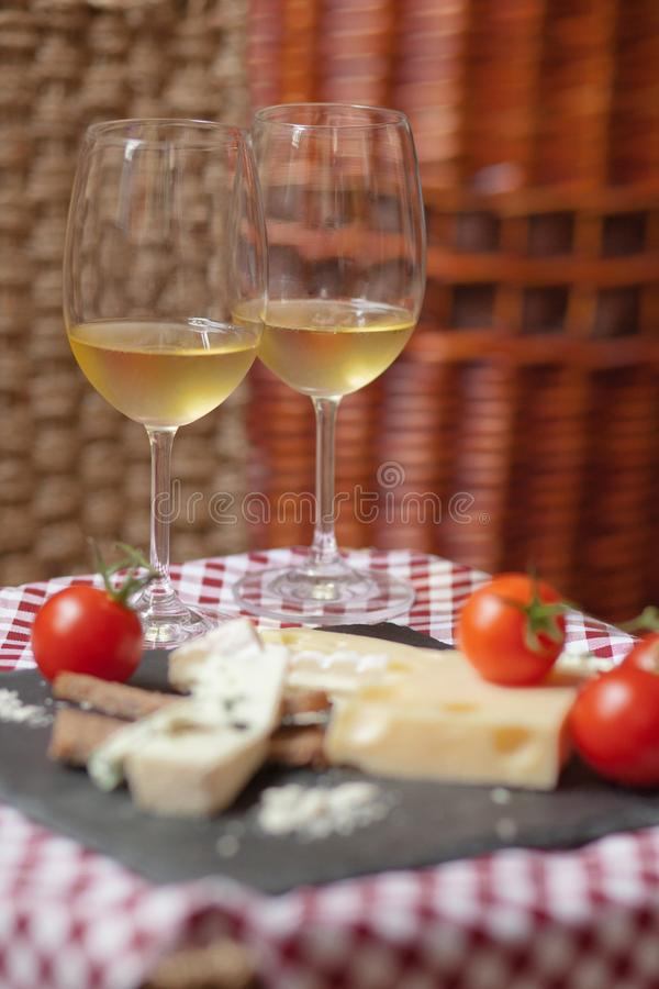 Romantic dinner for a couple on Saint Valentine`s day. Two glasses of cold white wine and gourmet french cheese plate with bread and fresh tomatoes. Nicely stock images