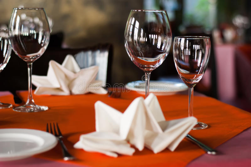 Romantic dinner interior, hotel service concept. Served table in a banquet hall. White plate knife fork and wine glasses. On red napkin. Soft focus royalty free stock image
