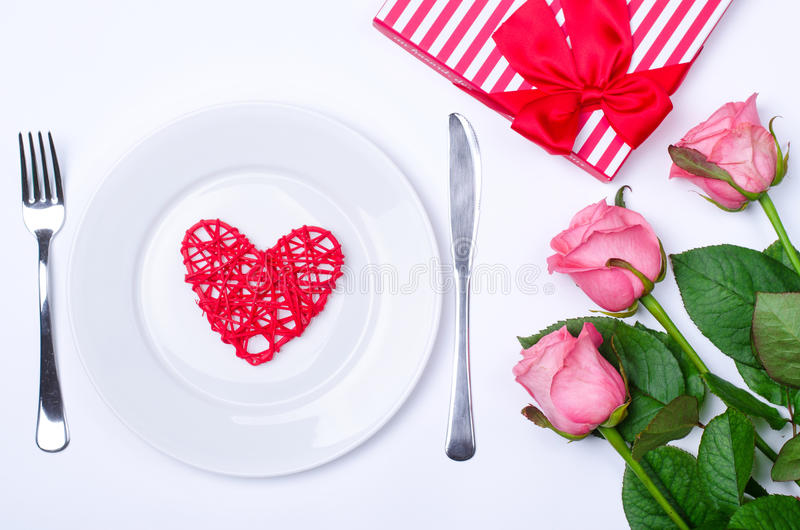 Romantic dinner: plate, cutlery and roses on a white background. The concept of the festive table: Birthday, Valentine& x27;s Day, wedding stock photography
