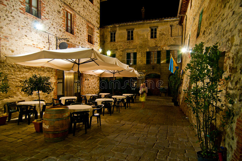 Romantic dinner in small Italian restaurant. Romantic dinner at night in a small Italian restaurant with outdoor garden royalty free stock photo