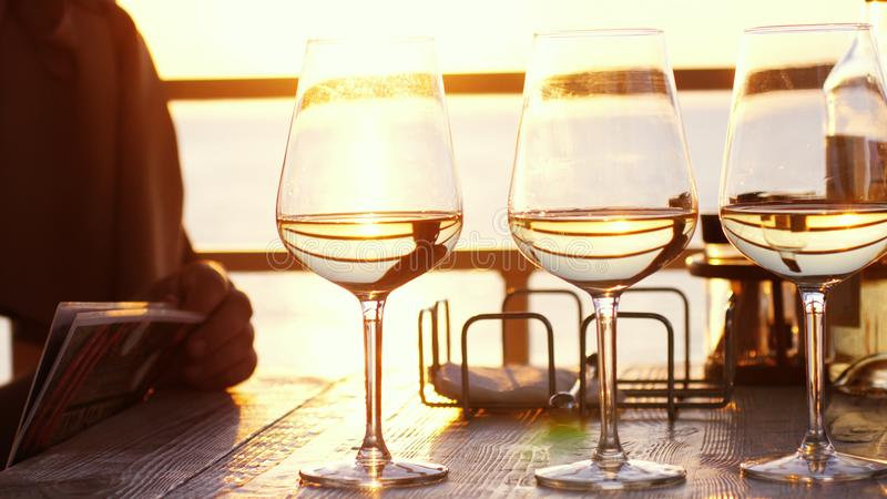 A romantic dinner in summer on a beach at sunset with three glasses of white wine and a bottle of the wine by the sea stock photography