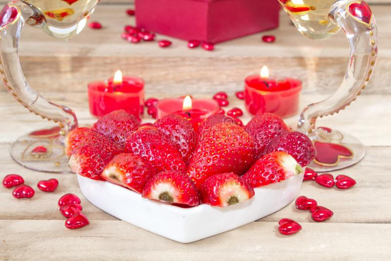 Romantic dinner on Valentine`s Day. Heart shaped plate with strawberries, heart shaped candles and two champagne glasses stock photos