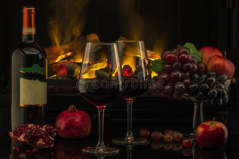 Romantic dinner with wine and grapes. On the background of the fireplace stock photos
