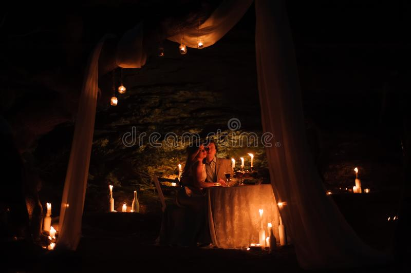Romantic dinner of a young couple by candlelight in the mountains. Romantic dinner of a young couple by candlelight in the mountains stock photo