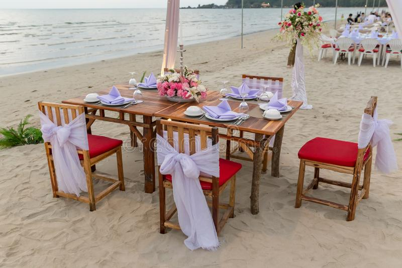 Romantic dinning table on the beach . Table setting at a luxury wedding and Beautiful flowers on the table. stock photo