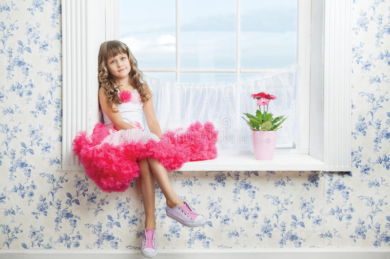 Romantic dreaming young girl sitting on windowsill royalty free stock images