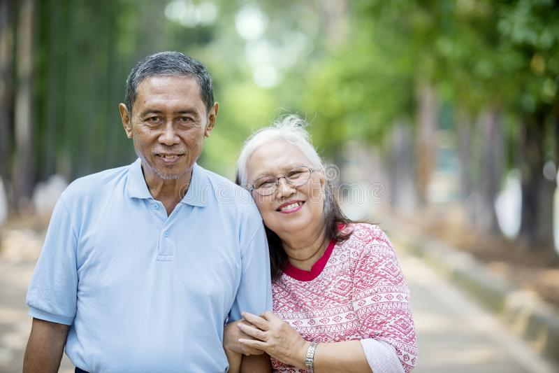 Romantic elderly couple standing on the road stock image