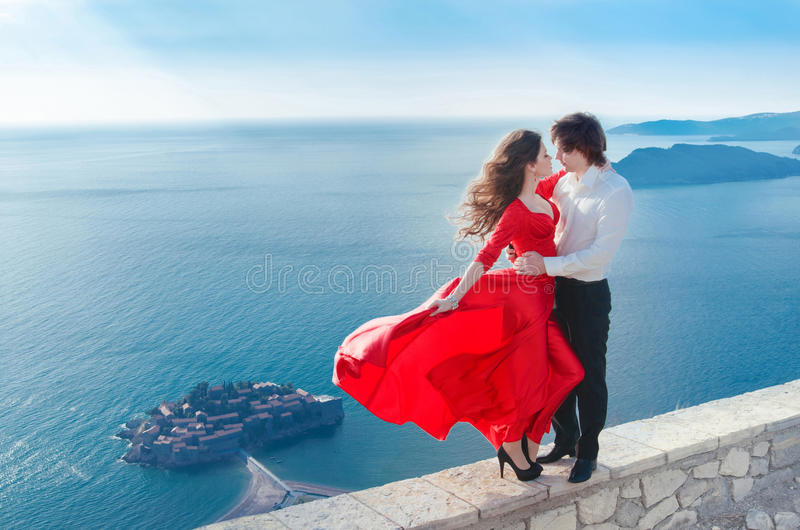 Romantic embracing couple beside blue sea in front of Sveti Stefan, Montenegro. Young woman with her groom. Travel. Vacations. royalty free stock image