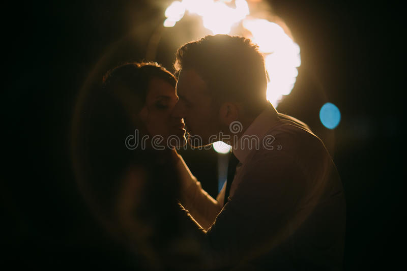 Romantic and emotional kiss of newlywed couple in front flaming heart. Night shot with lense flare stock photography