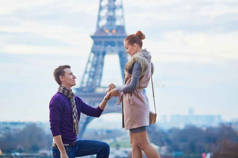 Romantic engagement in Paris. Men proposing to his beautiful girlfriend near the Eiffel tower royalty free stock images