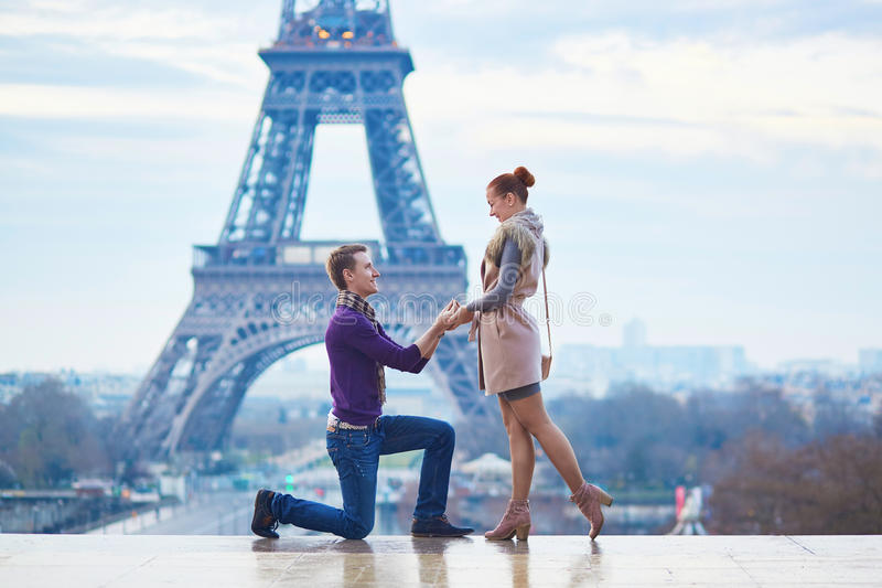 Romantic engagement in Paris. Men proposing to his beautiful girlfriend near the Eiffel tower stock image