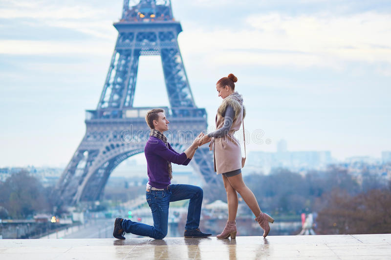 Romantic engagement in Paris. Men proposing to his beautiful girlfriend near the Eiffel tower stock photos