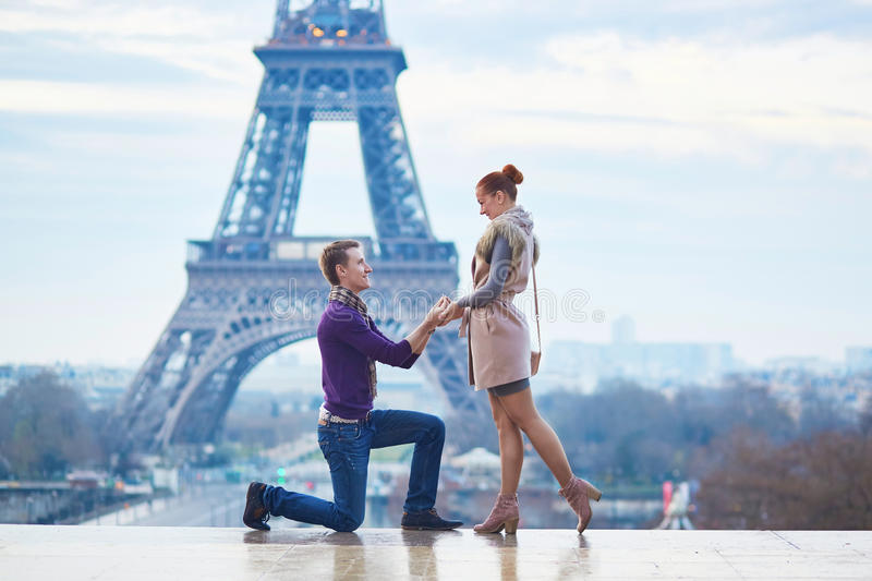 Romantic engagement in Paris. Men proposing to his beautiful girlfriend near the Eiffel tower royalty free stock photo