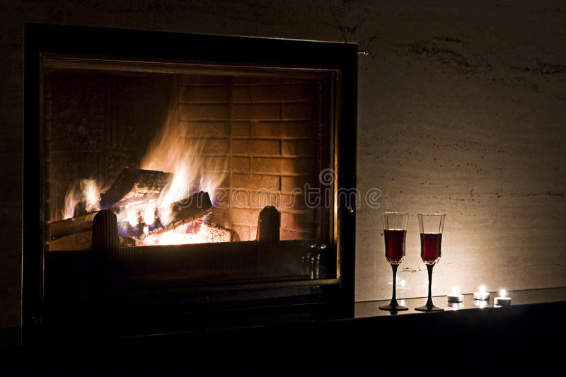 Romantic evening. For two: wine glasses, fireplace, lighted candles royalty free stock photography