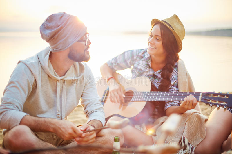 Romantic evening. Couple of campers spending romantic evening by seaside stock photography