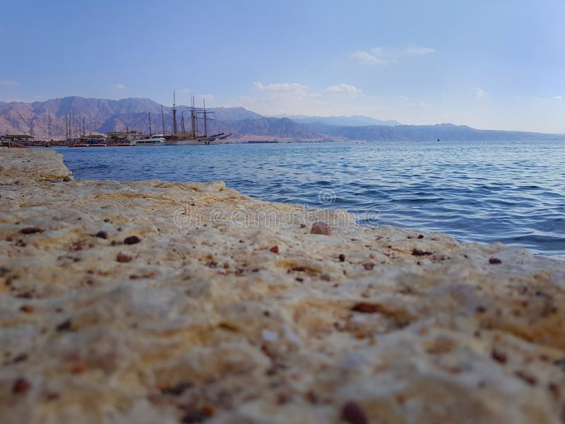Romantic evening at the rocky public beach near harbor in Eilat. Romantic evening at the Eilat city public beach, Israel. Harbor and Aqaba mountains, Jordan, in royalty free stock photography