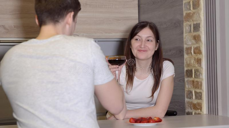 Romantic evening. Man and woman at a table with wine and strawberries. Romantic evening. Man and women at a table with wine and strawberries stock images