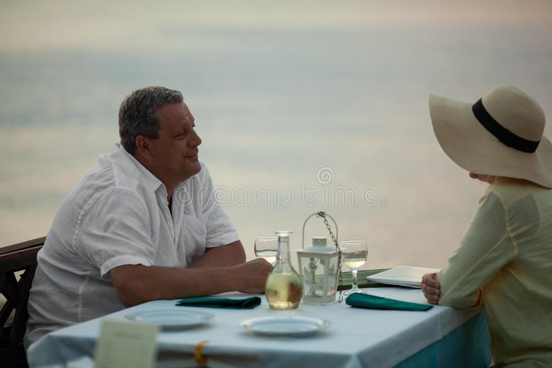Romantic evening for mature couple in the seafront restaurant stock photos