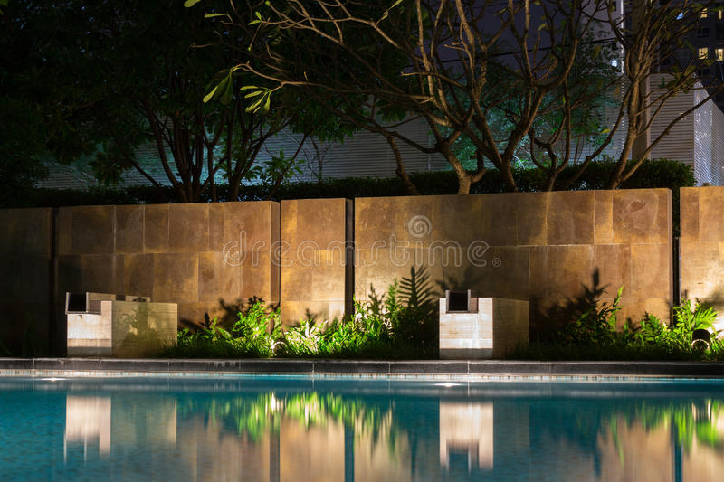 Romantic evening mood lighting casting shadows onto a romantic s. Etting near the pool. This luxury home has some of the best landscaped gardens and tropical royalty free stock photo