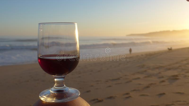 Romantic evening mood with a glass of red wine at the sea. Romantic evening mood at the sea. Armacao de Pera, Algarve, Portugal royalty free stock images