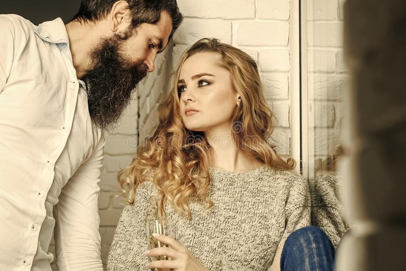 Romantic evening. Woman with glass look at bearded man. Couple in love enjoy wine. Holiday, party, celebration concept. Bad habit, addiction stock images