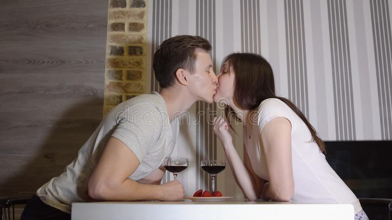 Romantic evening. A young couple at a table drinking wine and kissing.  stock photography