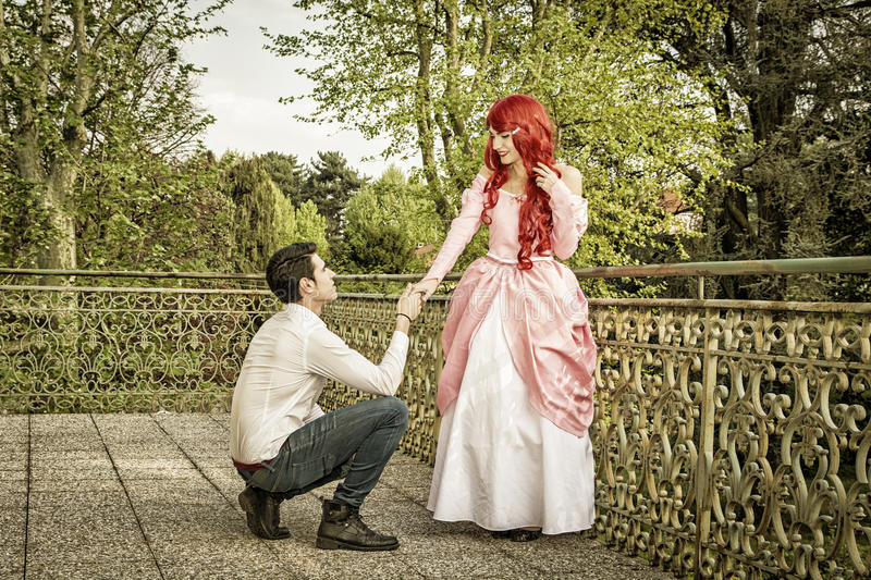 Romantic Fairy Tale Couple in Beautiful Palace. Garden in Peaceful Idyllic Setting, Man is Proposing to Woman, Prince and Princess Gazing at Each Other stock images