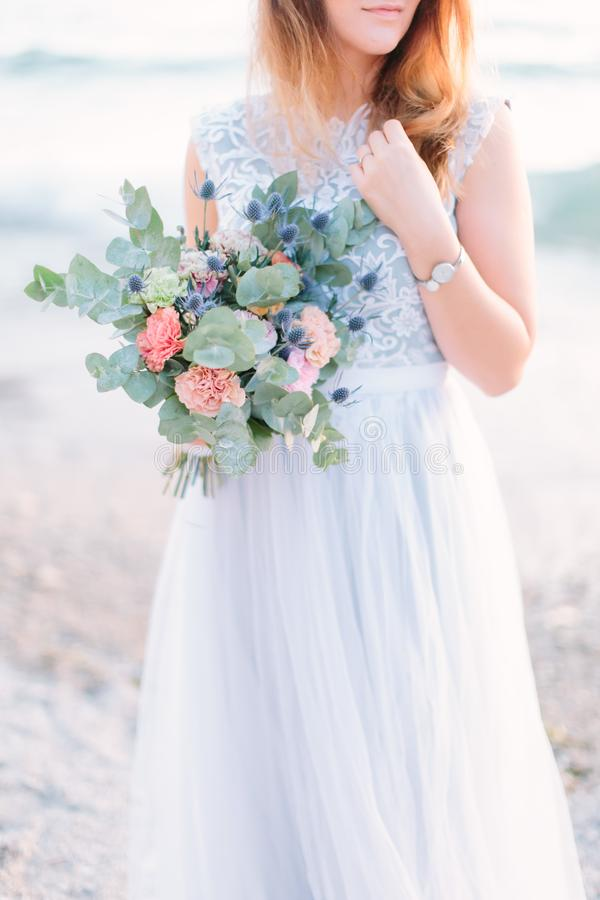 Romantic family concept. Young pretty woman in luxury blue wedding dress walking near the Garda Lake, Sirmione, Italy.  stock image