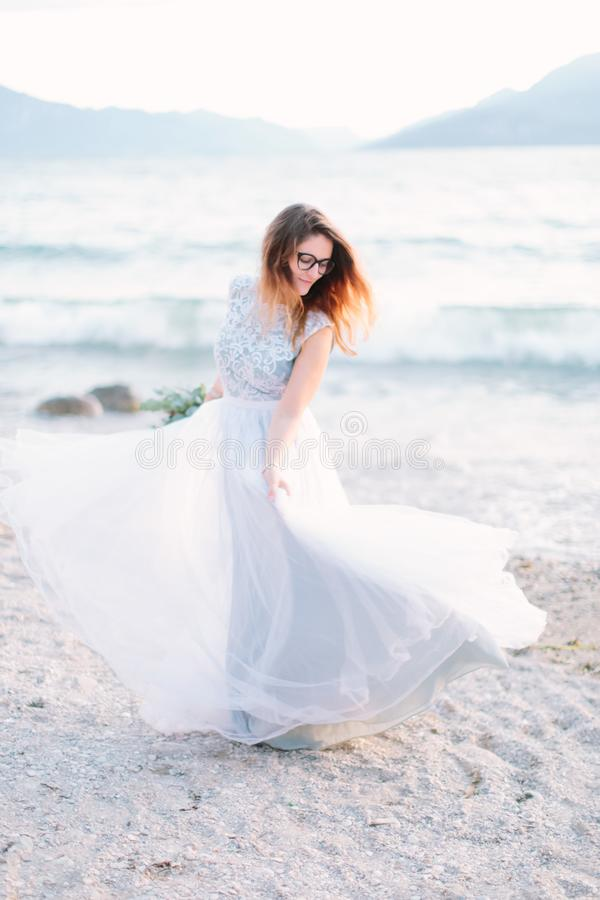 Romantic family concept. Young pretty woman in luxury blue wedding dress walking near the Garda Lake, Sirmione, Italy.  stock photos