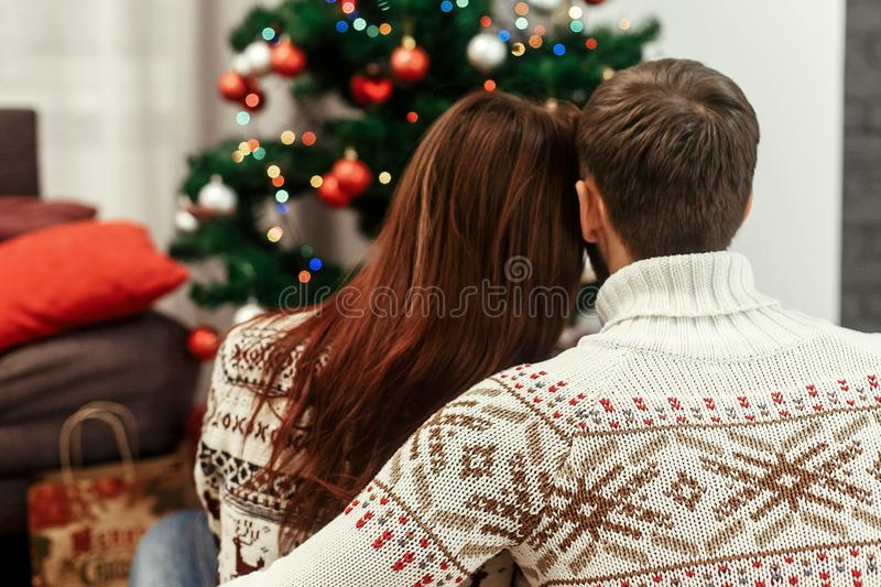 Romantic family couple in fashionable white sweaters hugging while looking at decorated christmas tree, greeting card concept wit royalty free stock images