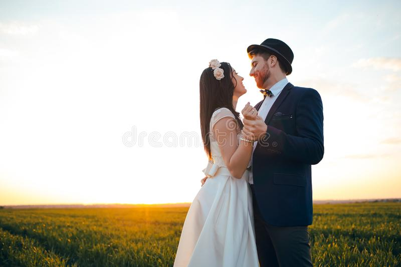 Romantic feelings in the field at sunset, the groom looks at the bride, the girl loves his boyfriend. The men is wearing a hat stock photos