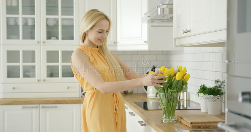 Romantic female composing bouquet. Wonderful young woman in romantic dress composing bouquet of yellow tulips while standing in light modern kitchen royalty free stock photo