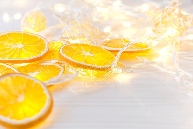Romantic festive background for postcard, banner: dried oranges circles and luminous garland stock images