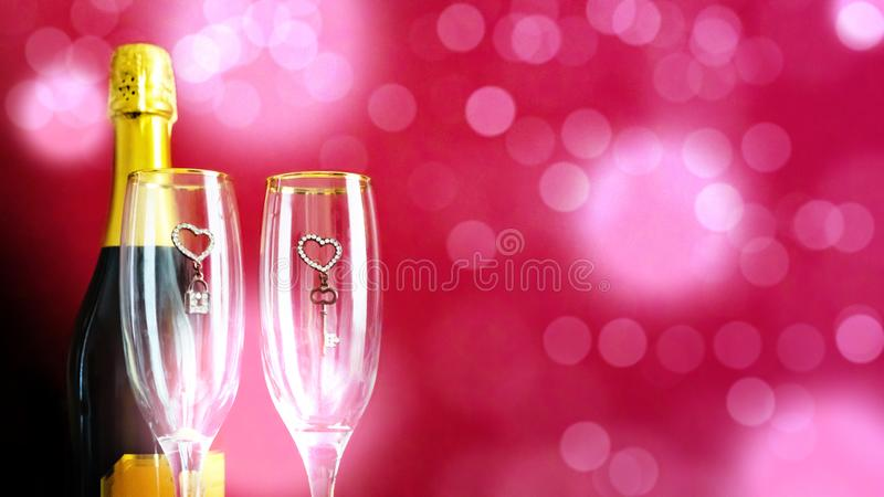 Romantic festive background with two glasses and champagne on a pink background with bokeh. The concept of love and celebration. royalty free stock images