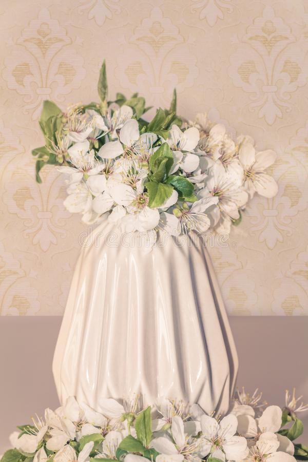 Romantic floral composition with white flowers close-up, spring blossom bouquet in a beige vase on vintage background royalty free stock image