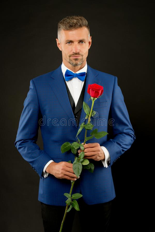 Romantic gentleman. Man mature confident macho with romantic gift. Handsome guy rose flower romantic date. Well groomed royalty free stock photos