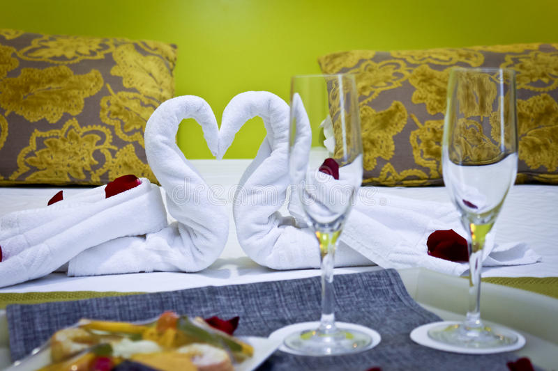 Romantic Getaway. With rose petals and towels shaped like swans on hotel bed royalty free stock images