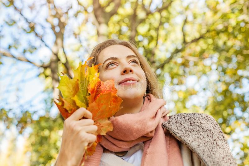 Romantic girl dreams in autumn fall park. Cute young woman holding yellow maple leaf outdoors royalty free stock image