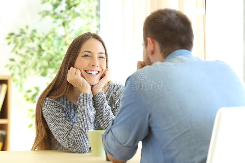 Romantic girl falling in love in a first date. Sitting in a table in the living room at home stock photography