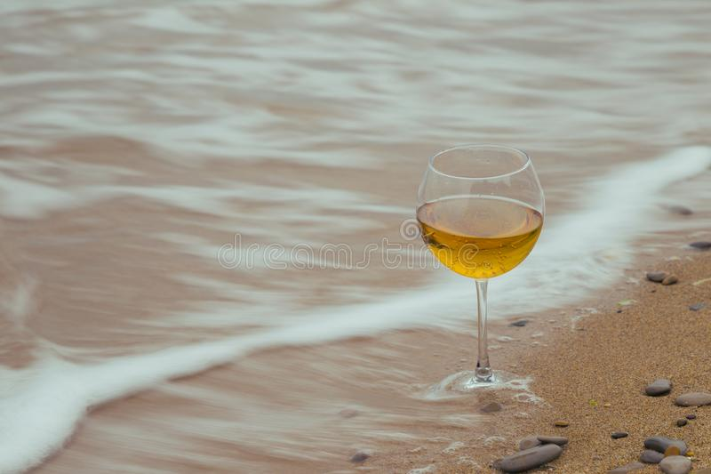Romantic glass of wine sitting on the beach,. Overcast autumn weather, cold wind stock photography