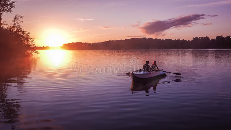 Romantic golden sunset river lake fog loving couple small rowing boat date beautiful Lovers ride during Happy woman man toget. A beautiful golden sunset on the royalty free stock photos
