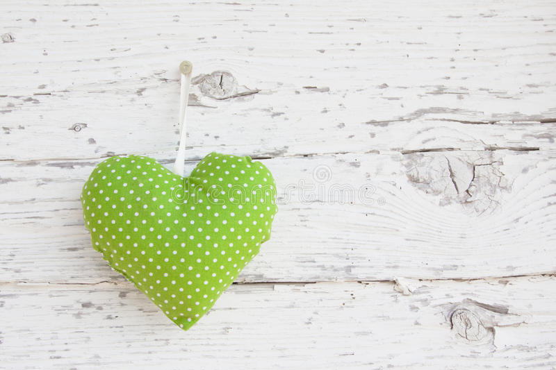 Romantic green dotted heart shape hanging above white wooden surface on a nail- white wooden shabby chic background for royalty free stock image