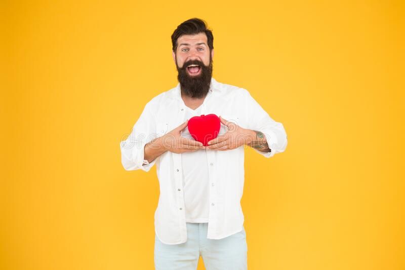 Romantic greeting. bearded man red heart. brutal hipster yellow background. happy valentines day. heart poblems and royalty free stock photo