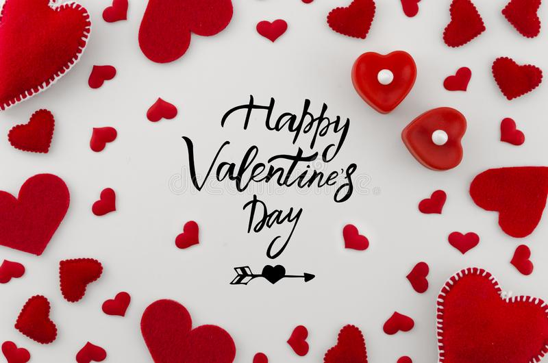 Romantic greeting card with hand written phrase happy valentines day in the center with different size red hearts on. White background. Valentines day top view stock photo