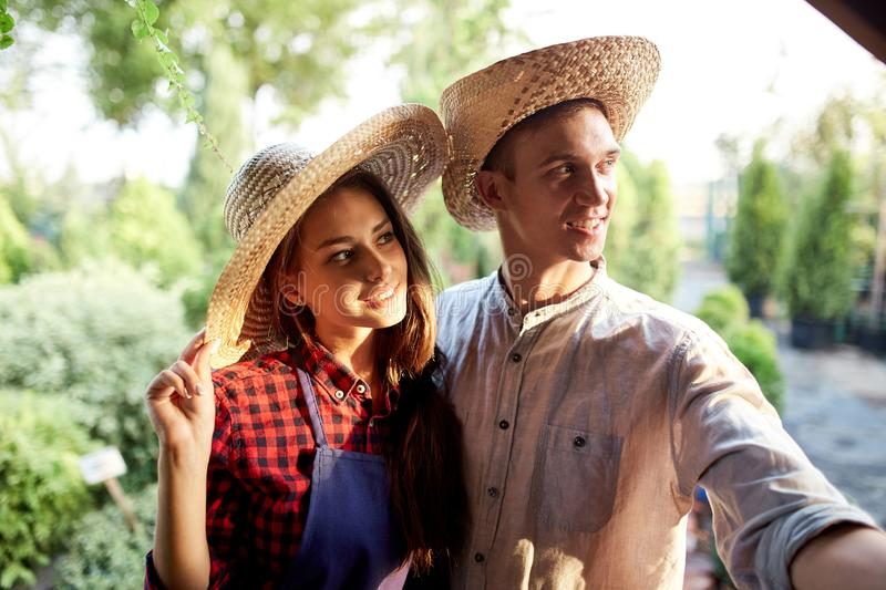 Romantic guy and girl gardeners in a straw hats are standing in the wonderful garden on a sunny day. royalty free stock image